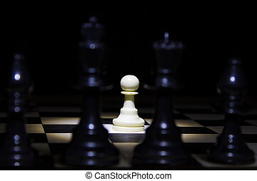 White pawn standing alone in spotlight on chess board between black pieces