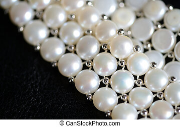 White pearl necklace on a dark background close up