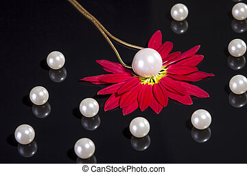 White pearls necklace on black background. Focus on the big...