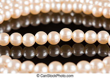 White pearls on black background. luxury necklace.