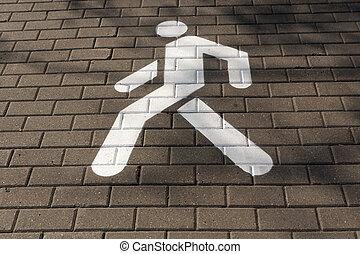White pedestrian sign on pavement.