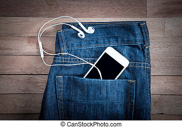 white phone in jeans pocket on a wooden background