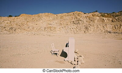 white piano and a white chair stand on a yellow sand against...