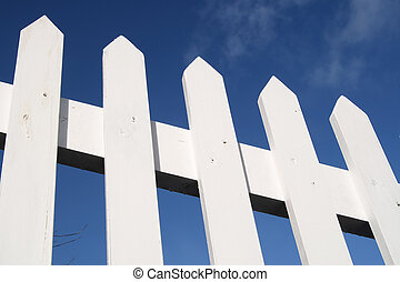 White picket fence and a blue sky.
