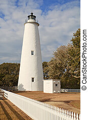 White picket fence leads past the tower of the Ocracoke Island lighthouse on the outer banks of North Carolina, the second-oldest operating lighthouse in the United States