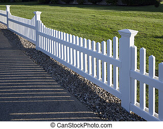White picket fence that delineates the grass from the...