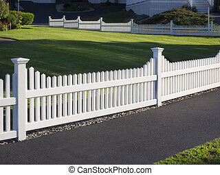 White picket fence that delineates the grass from the ...