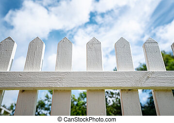 White picket fence under a blue sky