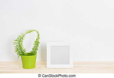 White picture frame and fern in green pot