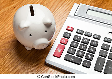 White Piggy Bank and calculator on wood table top