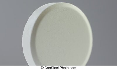 White pill rotate on a white background. Macro.