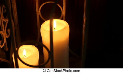 white pillar candles burning in an iron cage