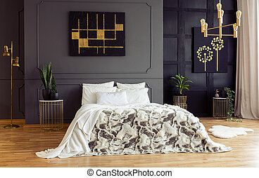 White pillows on patterned bed in grey bedroom interior with black and gold posters. Real photo