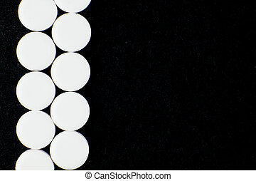 White pills on a black background