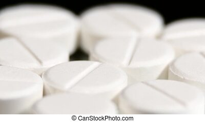 White pills, rotation, close up, on black