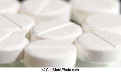 White pills, rotation, macro, on black