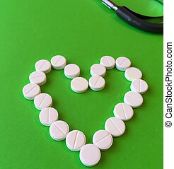 White pills, tablets placed in the shape of a heart on a green background. View from above. place for text