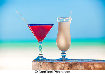 White pina colada and red margarita on the beach table