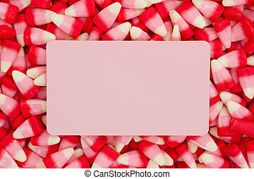 White, pink and red candy corn background with blank pink card