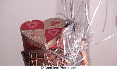 White, pink and silver helium balloons floating above heart-shape gift box