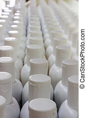 White plastic cream bottles in rows, cosmetics laboratory assembly line.