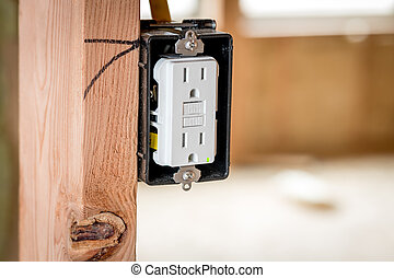 White plastic electrical outlet mounted in a box and a wood stud