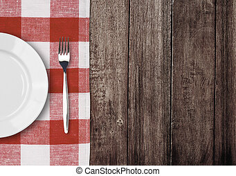 white plate and fork on old wooden table with red checked...