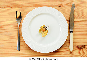 White plate and knife with a fork are served on a wooden table. view from above.