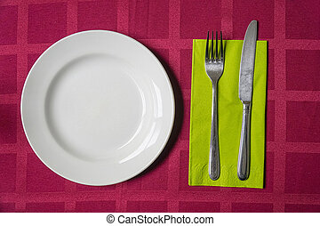White plate, fork and knife on a napkin