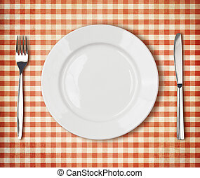 white plate, fork, knife top view over old red picnic tablecloth