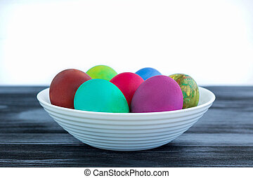 White plate of Easter multicolored boiled eggs on black wood