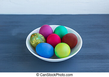 White plate of Easter multicolored boiled eggs on grey wood