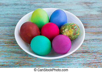 White plate of Easter multicolored boiled eggs on wooden background