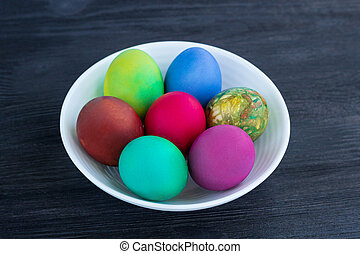 White plate of Easter multicolored eggs on black wood