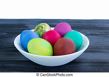 White plate of Easter multicolored eggs on black wooden background