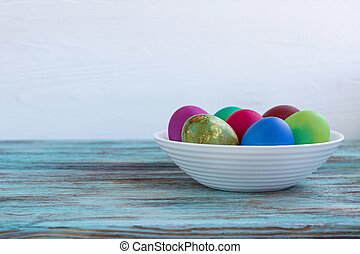 White plate of Easter multicolored eggs on wooden background
