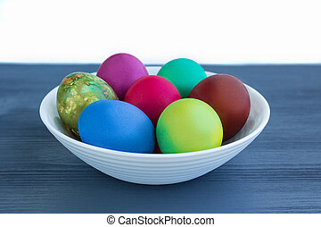 White plate of Easter versicolored boiled eggs on grey wood