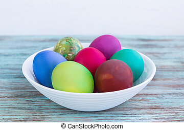 White plate of Easter versicolored boiled eggs on wooden background