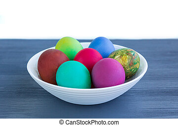White plate of Easter versicolored eggs on grey wood
