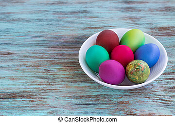 White plate of Easter versicolored eggs on wooden background