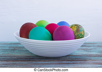 White plate of multicolored Easter eggs on wooden background