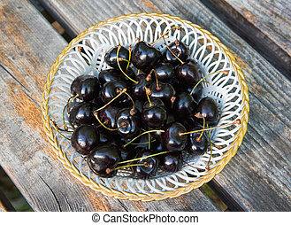 White plate of ripe black cherries with on a wooden table
