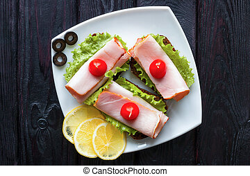 white plate on a black background with sandwiches