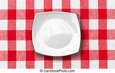 white plate on red checked fabric tablecloth