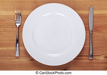 Photo of an empty white plate with knife and fork on a rustic wooden table.