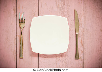 white plate, vintage fork and knife  on rustic pink wooden table. Top view point.