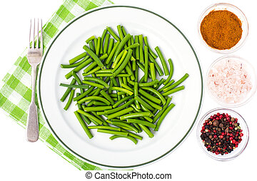 White plate with boiled green beans, top view
