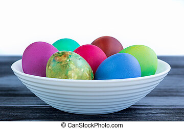 White plate with Easter multicolored boiled eggs on black wood
