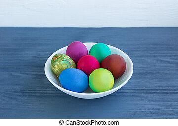 White plate with Easter multicolored boiled eggs on grey wood