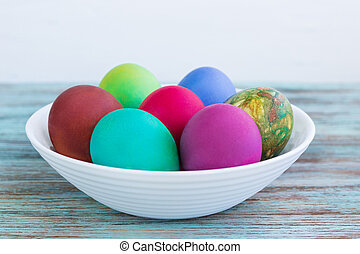 White plate with Easter multicolored boiled eggs on wooden background